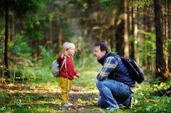 在森林里生和他的走在远足的活动期间的儿子 免版税库存图片