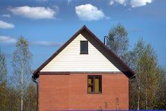 在森林附近的新的国家砖房子 免版税库存照片
