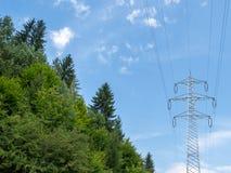 在森林附近的电定向塔 免版税图库摄影