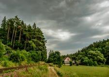 在森林附近的老房子在路和轨道旁边 库存照片