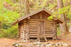 在森林隐藏的老固定的原木小屋风雨棚 库存图片