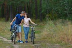在森林,在自行车的浪漫步行里结合亲吻 库存照片
