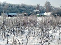 在森林,多雪的冬天边缘的土气房子 免版税库存照片