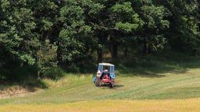 在森林,转动干草的机器附近的蓝色拖拉机轮,干草 影视素材