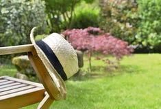在椅子上把放的草帽在庭院 免版税库存图片