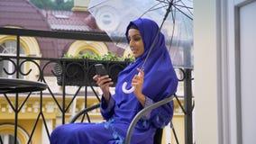 在椅子坐有伞的阳台和键入在手机的hijab的年轻回教妇女 股票视频