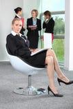 在椅子坐的女实业家 免版税库存图片