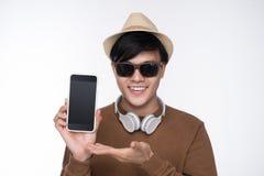 在椅子安装的聪明的偶然亚裔人,显示智能手机scree 库存图片