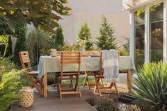 在椅子旁边的在房子大阳台的灯笼和桌有植物和毯子的 r 免版税库存照片