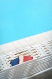 在椅子的书在游泳池边旁边 文本的空位 免版税库存图片