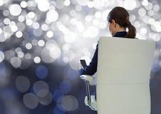 在椅子的女实业家后面开会与手机和bokeh闪耀的光 库存照片