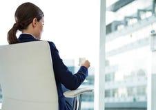 在椅子的女实业家后面开会与雪茄和大厦 免版税库存照片