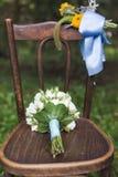 在椅子的婚礼花束 免版税库存照片