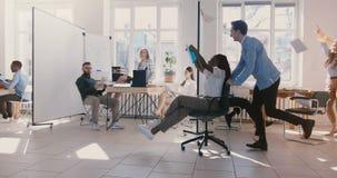 在椅子的慢动作成功的非裔美国人的办公室工作者妇女骑马获得乐趣,庆祝在健康办公室 影视素材