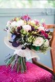在椅子的新娘婚礼花束 库存图片