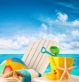 在椅子的海滩玩具由海洋 库存图片