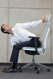 在椅子的瑜伽在办公室-商人行使 免版税图库摄影