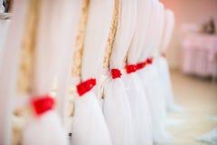 在椅子的白色婚礼装饰 免版税图库摄影