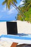 在椅子的膝上型计算机在海滩假期 免版税图库摄影