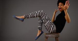 在椅子的黑人妇女跳舞 图库摄影