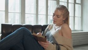 在椅子的年轻白肤金发的开会在窗口在日志的文字笔前面与一张皮面 a的一名美丽的妇女 影视素材