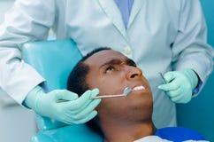 在椅子的年轻西班牙人得到与开放的嘴和生气表情,牙医手的牙齿治疗 库存照片