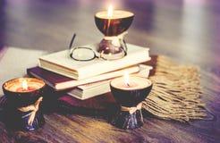 在椰子壳、枕头、玻璃和书,舒适家庭内部背景的燃烧的温泉芳香蜡烛 库存照片