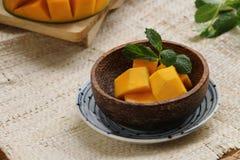 在椰子果壳碗的芒果立方体 库存图片