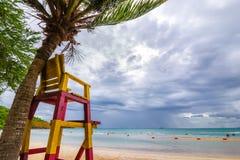 在椰子树附近的救生员椅子在与雨云的海滩 库存照片