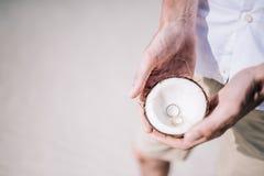 在椰子里面的定婚戒指在热带海滩 免版税库存图片