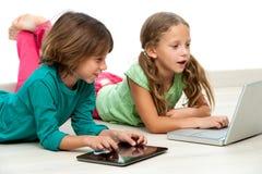 在楼层上的二个孩子与膝上型计算机和片剂。 图库摄影