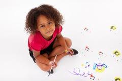 在楼层上的小的非洲亚洲女孩绘画 免版税图库摄影