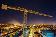 在楼房建筑站点的建筑用起重机沃罗涅日背景夜城市的 库存图片