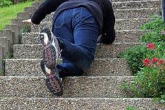 在楼梯滑倒的妇女和跌倒了 免版税库存图片
