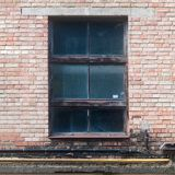 在楼梯间的老肮脏的破裂的窗口 免版税库存照片