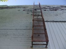 在楼1的边的一架生锈的梯子 库存图片