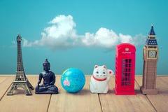 在概念旅行世界范围内 来自世界各地纪念品在蓝天背景的木桌上 免版税图库摄影