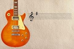 在概略的纸板背景的左边梯级和蜂蜜镶有钻石的旭日形首饰的葡萄酒电吉他 图库摄影