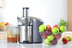 在榨汁器机器的苹果汁- juicing 免版税图库摄影