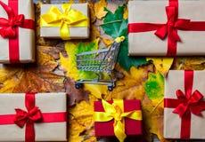 在槭树的礼物盒离开与购物车 库存图片
