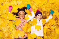 在槭树盖的非洲和白种人女孩离开 免版税库存照片
