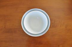 在槭树表上的被筑巢的白色碗 免版税库存图片