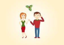 在槲寄生下的圣诞节夫妇 免版税库存图片