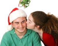 在槲寄生之下的圣诞节亲吻 免版税库存照片