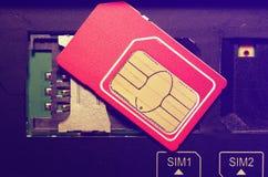 在槽孔的红色西姆卡片在手机 库存照片