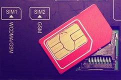 在槽孔的红色西姆卡片在手机 库存图片