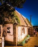在槽枥和美丽的天空旁边的一个老房子 免版税库存图片