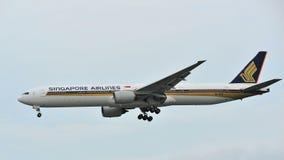 在樟宜机场的新航波音777着陆 库存图片