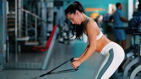 在模拟器的俏丽的女孩训练在健身房 股票视频
