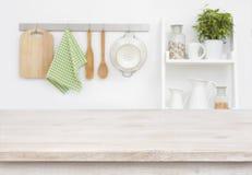 在模糊的厨房墙壁和架子背景的木纹理桌 免版税库存图片